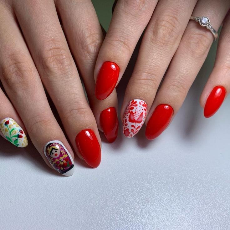 Красный миндальный маникюр на средние ногти с национальными рисунками и матрешкой